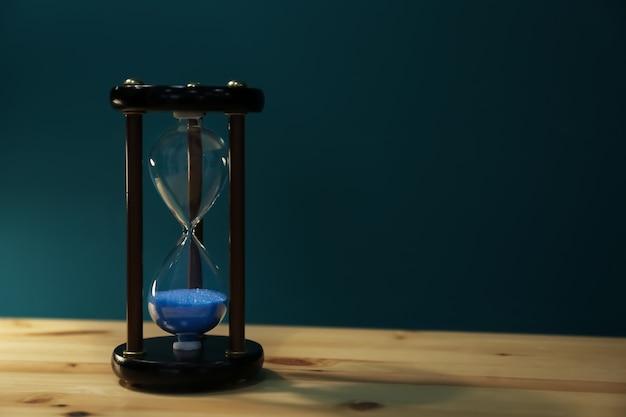 Kristalzandloper op tafel tegen een achtergrond met kleur. tijdmanagementconcept