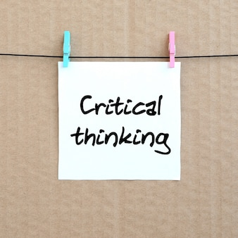 Kritisch denken. opmerking staat op een witte sticker die met een wasknijper aan een touw op een achtergrond van bruin karton hangt