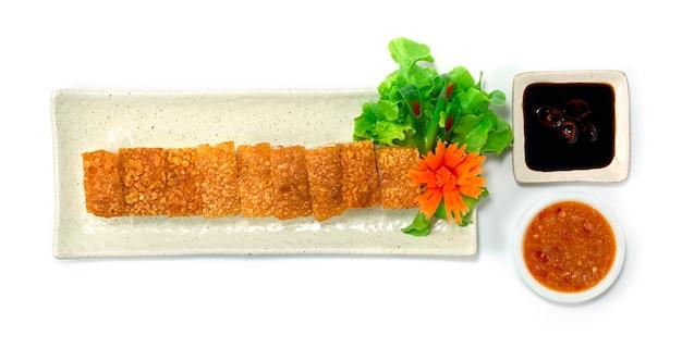 Krokant buikvarkensvlees hong kong-stijl bruine huid zo krokant geserveerd zwarte sojasaus en dipsaus met zeevruchten versier wortel en groente bovenaanzicht