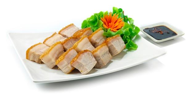 Krokant buikvarkensvlees hong kong-stijl bruine huid zo krokant geserveerd zwarte sojasaus versier wortel en groente zijaanzicht