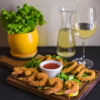 Krokant gebakken garnalen en calamaris geserveerd met citroen en zoete chilisaus