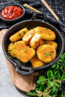 Krokant gebakken kipnuggets in een pan met ketchup en kruiden