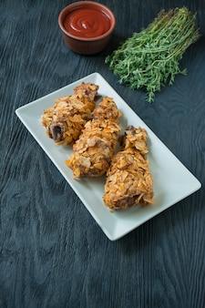 Krokant gebakken kippenpoten gepaneerd met frietjes. fast food. verkeerd eten. donkere houten tafel. ruimte voor tekst.