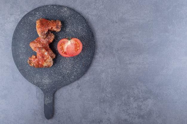 Krokant gebakken vleugels en tomaat op zwart bord.