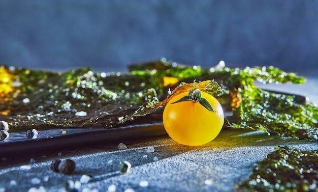 Krokant nori zeewier met kerstomaatjes en donkere kruiden op grijs beton. japans eten nori. gedroogde vellen zeewier. kopieer ruimte
