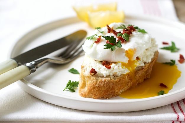 Krokant stokbrood toast met kwark, gepocheerd ei en gedroogde tomaten op een lichte achtergrond.