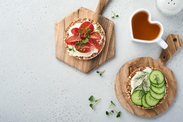 Krokante boekweitbroodcake glutenvrij met roomkaas, rode radijs, tomaten en microgroen voor een gezond ontbijt op grijze stenen achtergrond. uitzicht van boven. concept veganistisch en gezond eten.