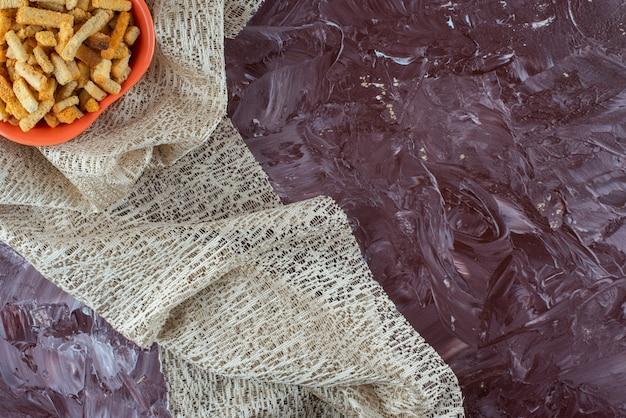 Krokante broodkruimels in een kom op een tafelkleed, op de marmeren tafel.