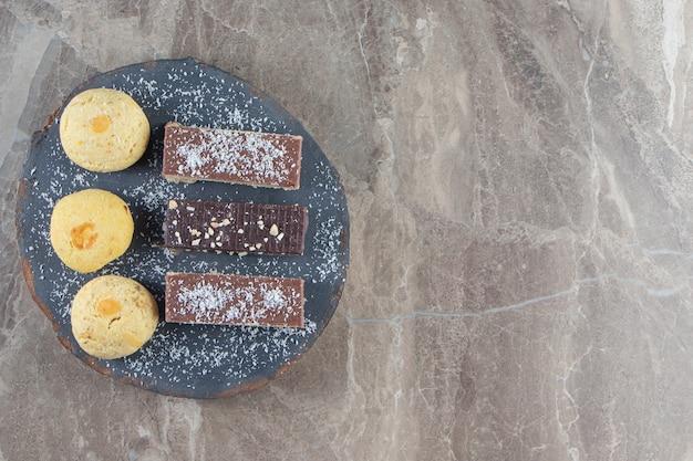 Krokante chocoladewafel en zandkoek aan boord op marmer.