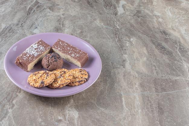 Krokante chocoladewafel en zelfgemaakte koekjes op een bord op marmer.