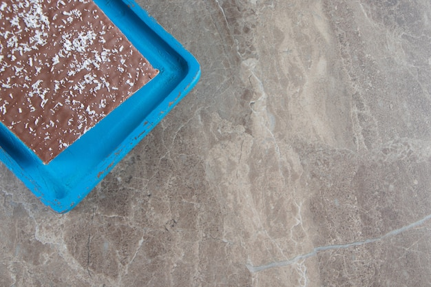 Krokante chocoladewafel op houten plaat op marmer.