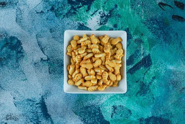 Krokante cracker vis in een kom, op de blauwe tafel.