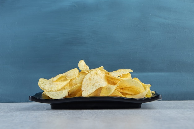Krokante gegolfde chips op zwarte plaat en gestreept tafelkleed.
