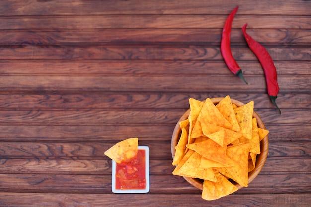 Krokante gouden maïstortilla's met hete salsasaus en een roodgloeiende chili peper voor een pittige snack