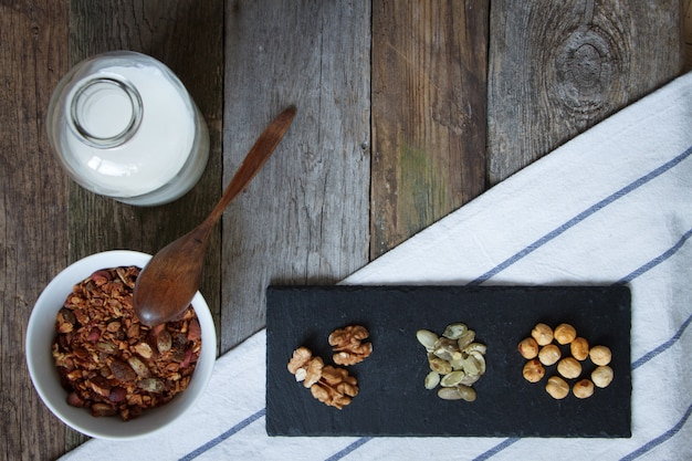 Krokante honinggranolakom met lijnzaad, veenbessen, een fles melk en een hoop noten op een zwarte standaard op een tafel