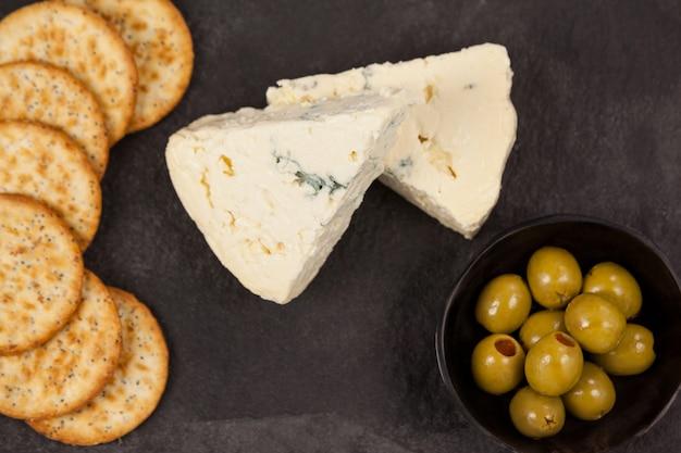 Krokante koekjes, kaas en kom van groene olijven op snijplank