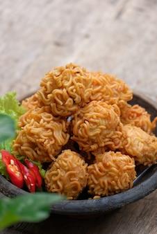 Krokante noedelballen geserveerd op een kom, ook bekend als bola bola mie