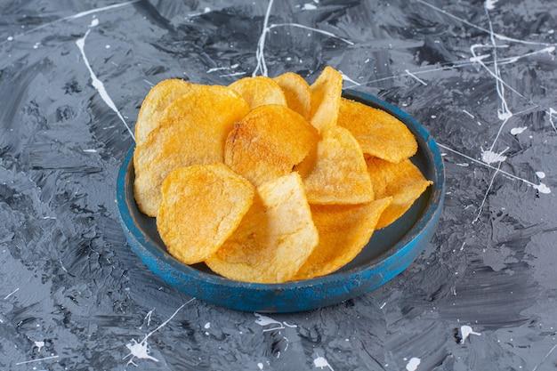 Krokante, pittige chips in houten plaat, op het marmeren oppervlak