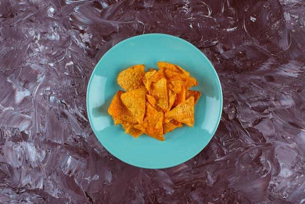 Krokante pittige chips op een bord, op de marmeren tafel.