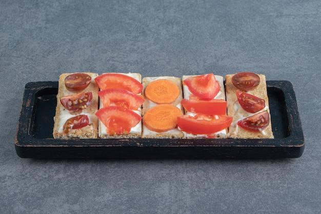 Krokante toast met tomaten op een houten bord.