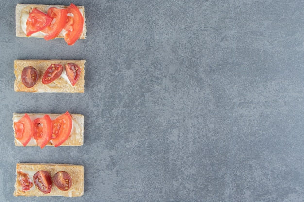 Krokante toast met tomaten op marmer.