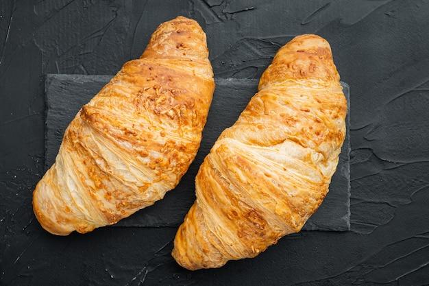 Krokante verse croissants set, op zwarte stenen achtergrond, bovenaanzicht plat lag