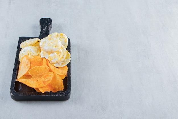 Krokante volkoren rijstwafels en chips op zwarte snijplank.