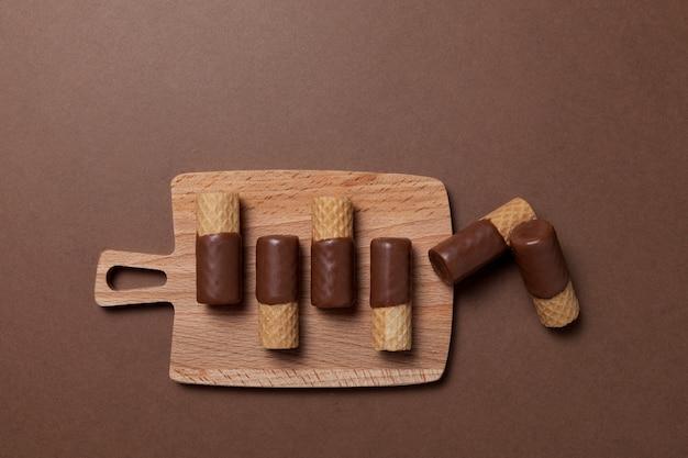 Krokante wafelrolletjes half omhuld met melkchocolade op serveerplank