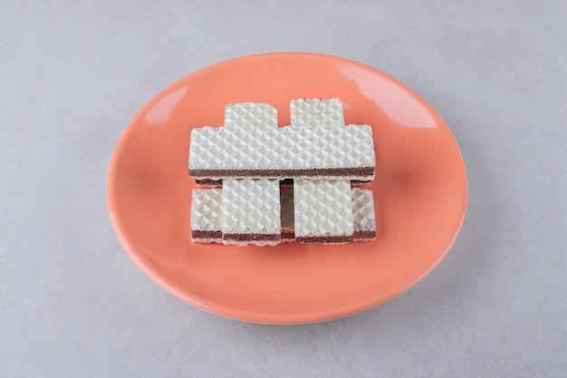 Krokante wafels op een bord op marmeren tafel.