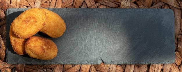 Kroketten gepresenteerd op blackboard met ruimte voor tekst. horizontaal panoramisch uitzicht.