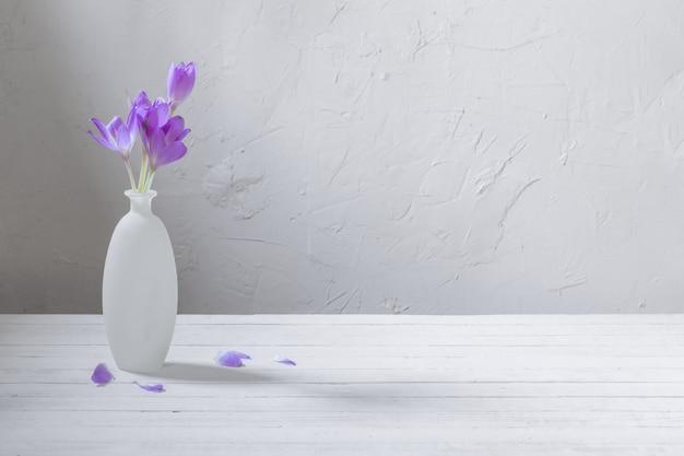 Krokus op glazen vaas op witte achtergrond