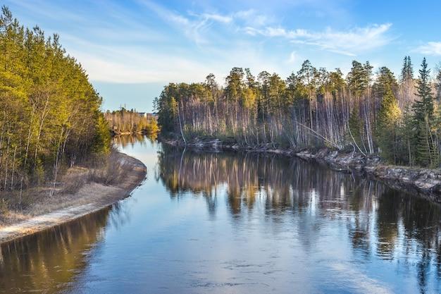 Kronkelende rivier op een zonnige herfstdag met boom reflecties