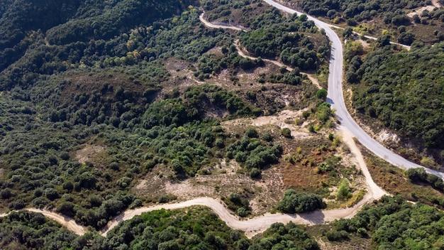 Kronkelende weg, heuvels bedekt met weelderig groen, uitzicht vanaf de drone, griekenland