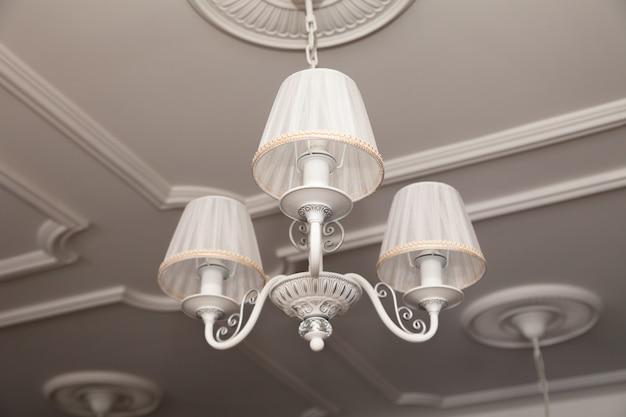 Kroonluchters met drie elektrische lampen en lampenkappen die aan het plafond hangen
