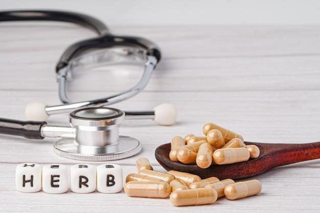 Kruid belettering en stethoscoop met geneeskunde kruiden capsule