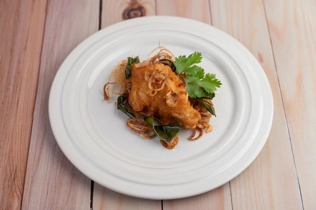 Kruid gebakken kip op een witte plaat op een houten vloer.