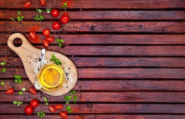 Kruiden, cherry tomaten, basilicum en plantaardige olie op donkere houten tafel, bovenaanzicht