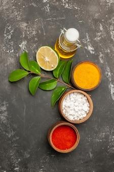 Kruiden drie kommen kruiden citroen met blaadjes naast de fles olie aan de rechterkant van de donkere tafel