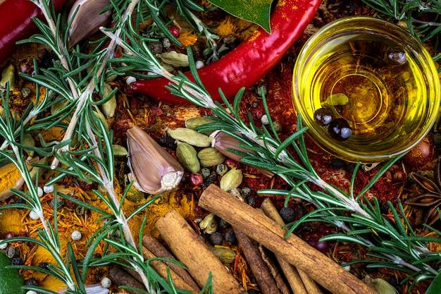 Kruiden en gemorste kruiden, takken van rozemarijn en kaneelstokje, kardemon, olijfolie als achtergrond.