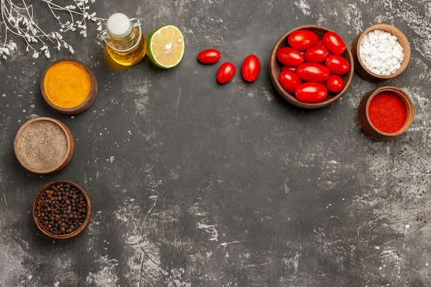 Kruiden en kommen met kleurrijke kruiden, fles olie, citroen en tomaten op de donkere tafel