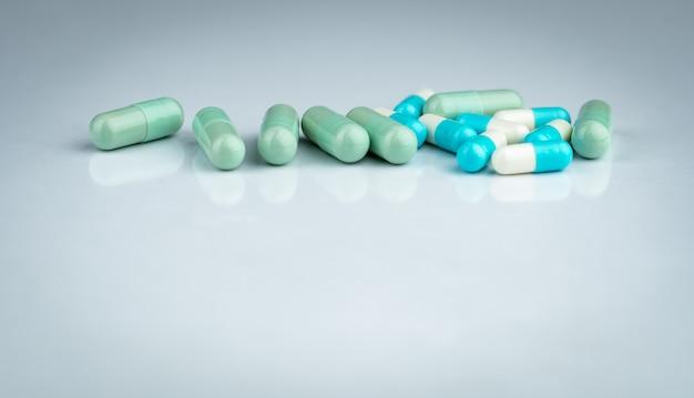 Kruiden- en medicijninteracties. groene en blauwe capsulepil op witte achtergrond. kruidenmedicijn. farmaceutische industrie. apotheek drogisterij achtergrond. farmacie. wereldwijde gezondheidszorg. farmacologie.