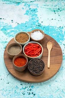 Kruiden en peper met zout op lichtblauw