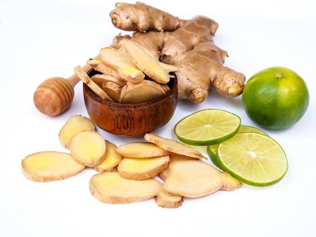 Kruiden en specerijen met gemberwortel en limoen citroen citrus en honing geïsoleerd op witte ruimte.