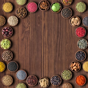 Kruiden en specerijen op houten tafel achtergrond. veelkleurige zeeën