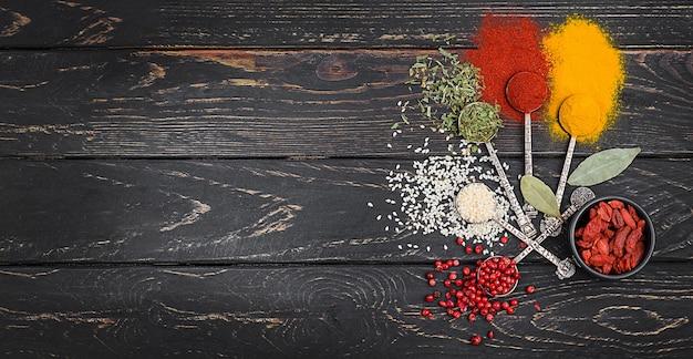 Kruiden en specerijen voor het koken in oude lepels geschoten op houten achtergrond.