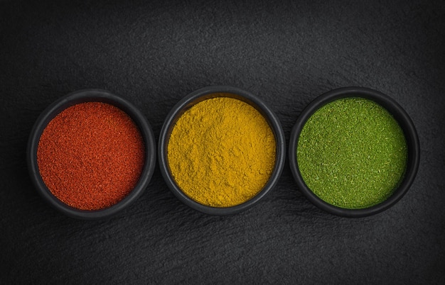 Kruiden en specerijen voor het koken op zwarte stenen plaat. paprika, kurkuma en gedroogd laurierblad. ziet eruit als verkeerslichten.