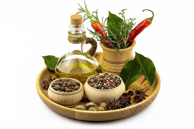 Kruiden in houten serviesgoed, verse scherpe cayennepeper, takken van rozemarijn en laurierblad in een houten vijzel, olijfolie, geïsoleerd op een witte tafel.