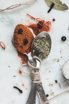 Kruiden in verschillende lepels op stenen marmeren tafel. rustiek vintage kleurtoon