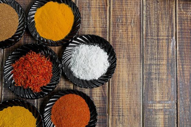 Kruiden in zwarte keramische platen op houten achtergrond. diverse specerijen selectie. zes borden met verschillende kleurrijke kruiden, bovenaanzicht.
