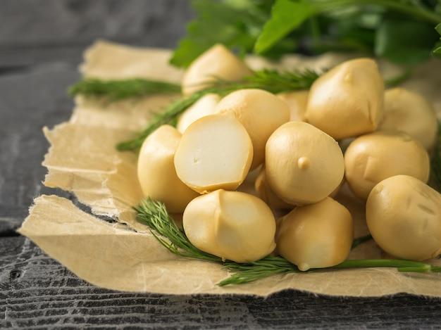 Kruiden met ballen van vers gemaakte mozzarellakaas op een houten tafel